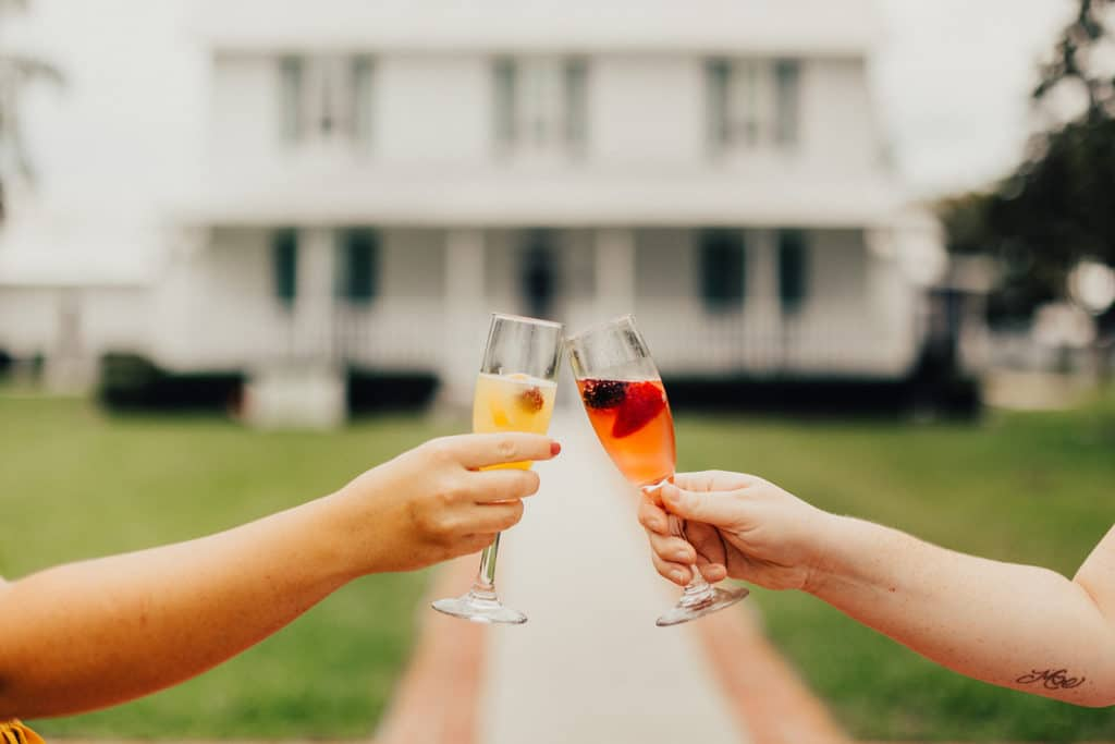 two women toasting champagne glasses in front of Field Manor on Merritt Island, FL